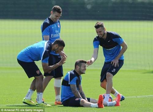 Joking around: Wilshere's team-mates gang up on him after losing a forfeit