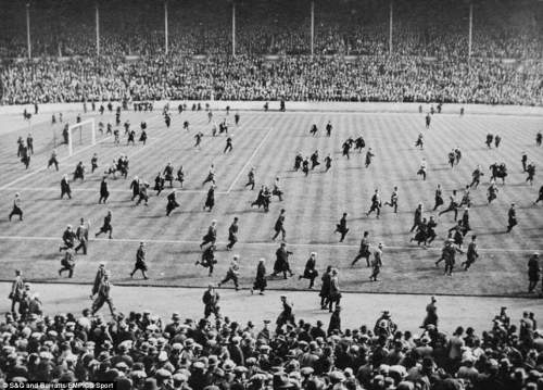 Crowds on the pitch after the final whistle celebrating Cardiff City's 1-0 win over Arsenal in 1927