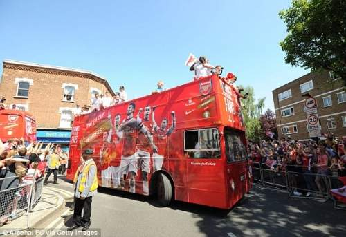 Setting off: Arsenal players set on board one of the buses as the sun shines down on north London
